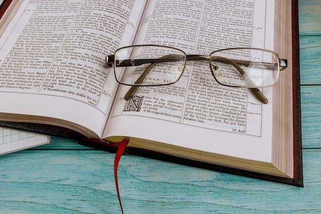 Mesa de escritorio abrió la santa biblia cerca del tiempo de oración en anteojos