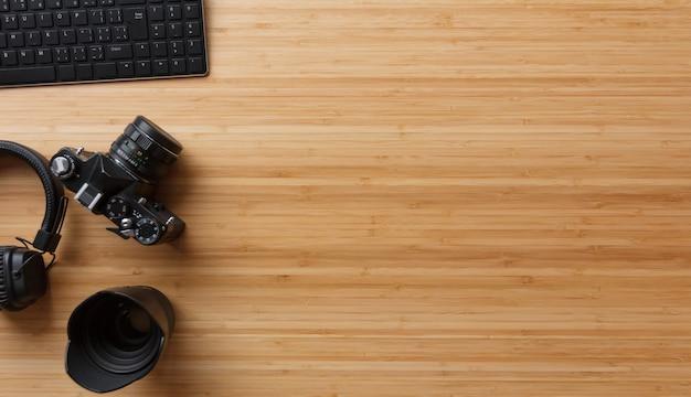 Mesa de escritorio de bambú del fotógrafo con cámara de cine, computadora portátil, auriculares y suministros. vista superior, plano, copia espacio.