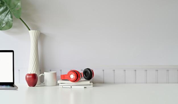 Mesa de escritorio blanca con espacio de copia. vista frontal del espacio de trabajo, portátil y espacio de copia.