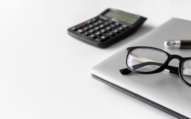 Mesa de escritorio blanca con útiles de oficina, notebook y lentes.