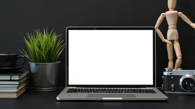 Mesa de escritorio de fotografía de oficina oscura con portátil de pantalla en blanco