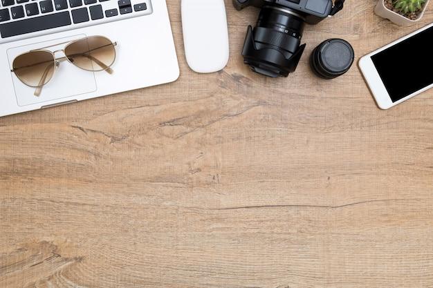 Mesa de escritorio para fotógrafos de madera con cámara, lente de cámara, laptop, teléfono inteligente y suministros.