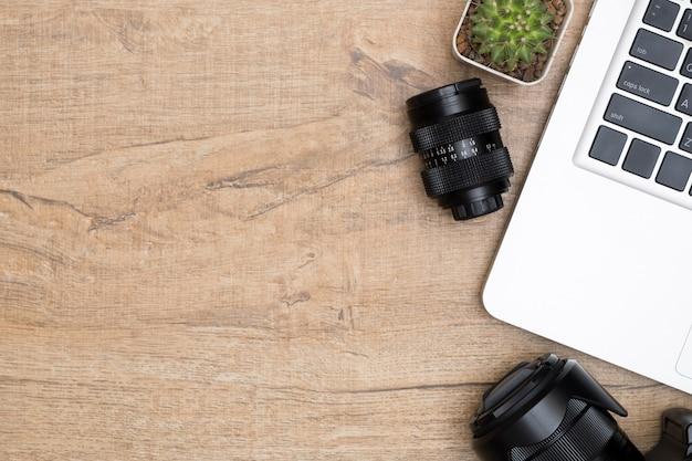 Mesa de escritorio de madera con cámara, lente y laptop.