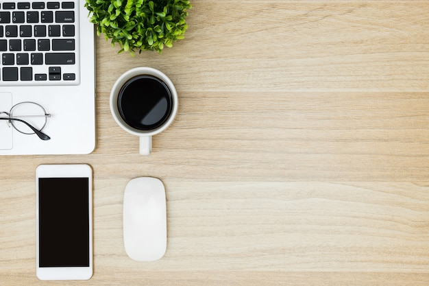 Mesa de escritorio de madera con ordenador portátil, café, teléfono inteligente y suministros.