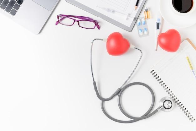 Mesa de escritorio médico con estetoscopio y corazón rojo