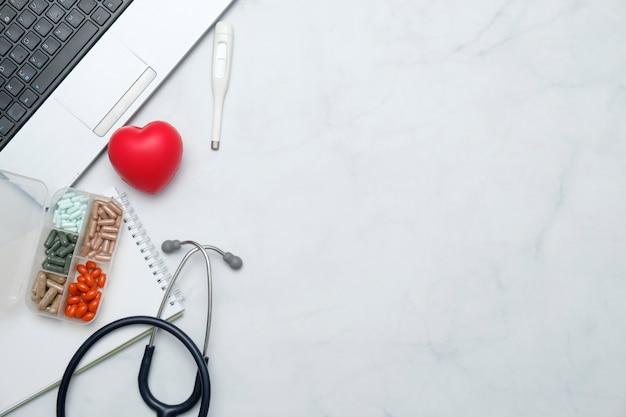 Mesa de escritorio médico con estetoscopio, medicina, cuaderno, material de oficina.