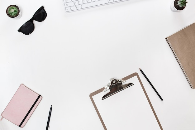 Mesa de escritorio moderna de blogger blanco con teclado blanco, tableta, cactus y diario rosa