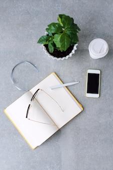 Mesa de escritorio de oficina con agenda portátil, teléfono inteligente, gafas, cafeto y taza de café.