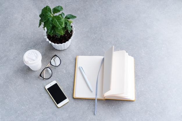 Mesa de escritorio de oficina con agenda portátil, teléfono inteligente, vasos y taza de café.