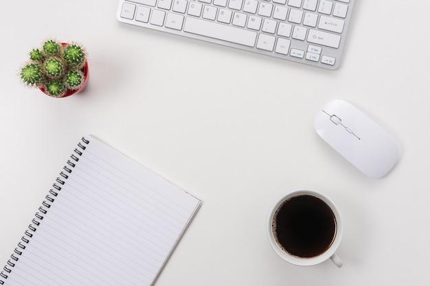 Mesa de escritorio de oficina blanca con cuaderno en blanco, teclado de computadora y otros suministros de oficina.