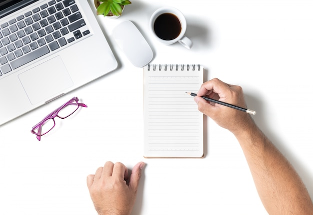 Mesa de escritorio de oficina blanca con hombre de la mano escribiendo en el cuaderno en blanco