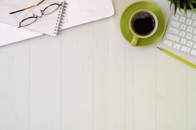 Mesa de escritorio de oficina blanca con laptop, café y espacio de copia
