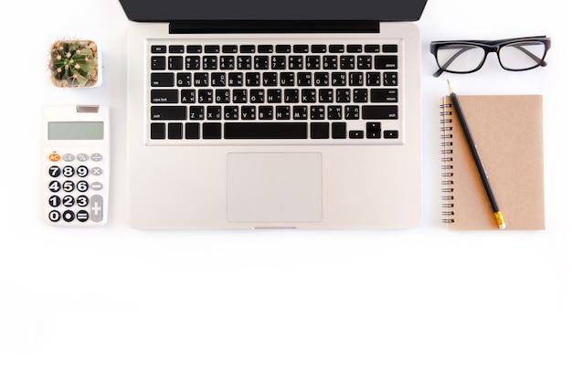 Mesa de escritorio de oficina blanca, oficina de espacio de trabajo con computadora portátil, pantalla negra para smartphone, pluma, calcu