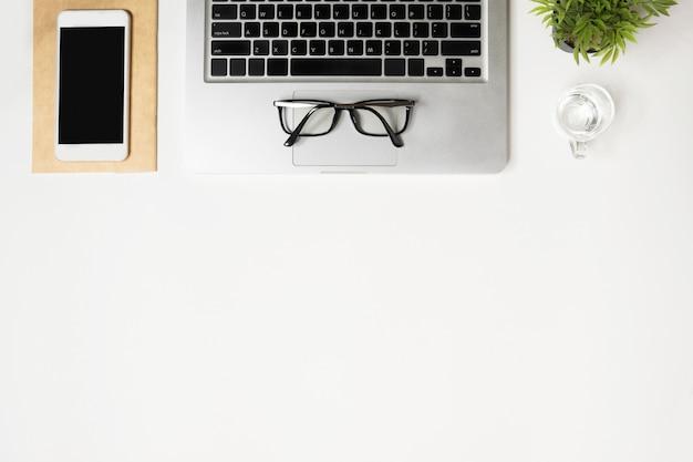 Mesa de escritorio de oficina blanca con ordenador portátil, teléfono inteligente y suministros. vista superior con copyspace, endecha plana.