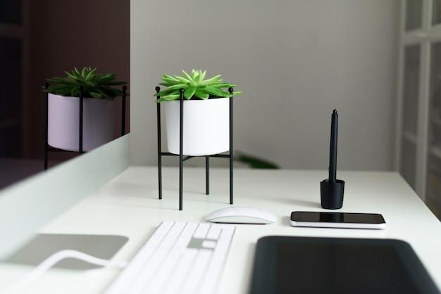 Mesa de escritorio de oficina blanca con teclado, mouse, monitor, tableta gráfica, teléfono inteligente, planta suculenta y otros suministros de oficina.