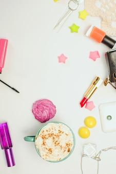 Mesa de escritorio de oficina blanca con teléfono inteligente, cámara vintage, café con especias y cosméticos.