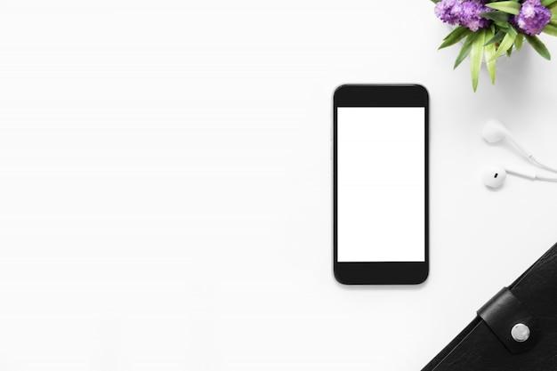 Mesa de escritorio de oficina blanca con teléfono inteligente con pantalla en blanco y otros suministros de oficina.