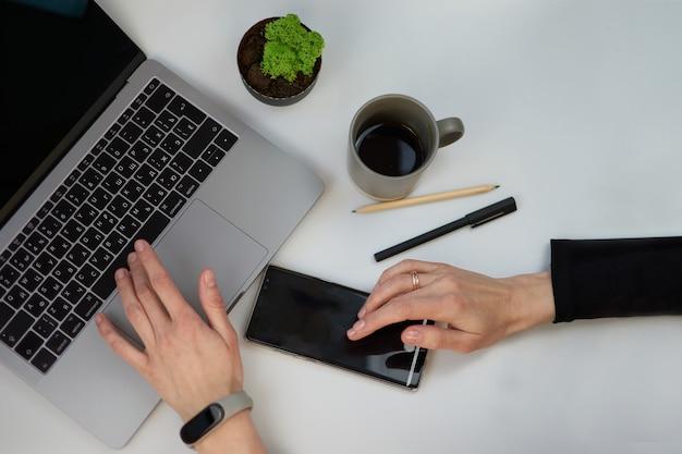 Mesa de escritorio de oficina blanca de vista superior con cuaderno en blanco, teclado de computadora portátil, bolígrafo, planta y otros suministros de oficina. taza de café con espacio de copia, endecha plana. manos de mujer con teléfono.