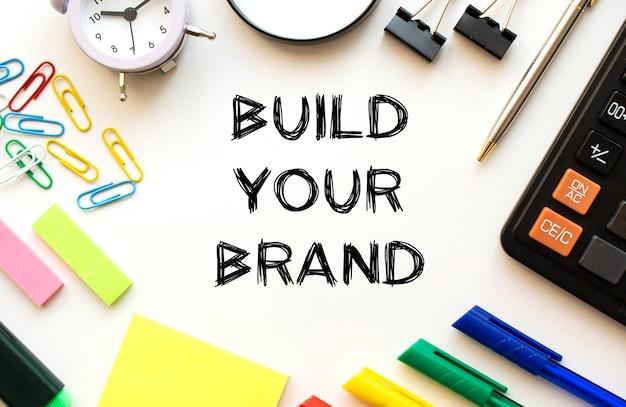 Mesa de escritorio de oficina con calculadora, bolígrafos y otros artículos de papelería. texto en construye tu marca.