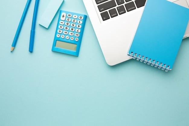 Mesa de escritorio de oficina con computadora portátil, cuaderno, lápiz, borrador, calculadora. endecha plana