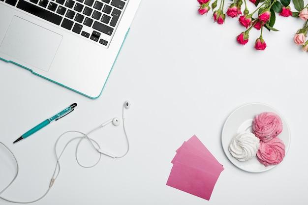 Mesa de escritorio de oficina con computadora, suministros y flores.
