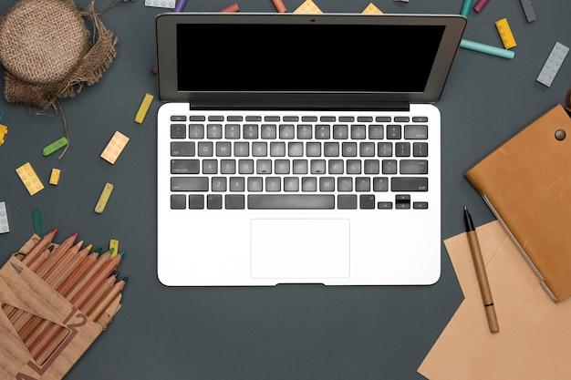 Mesa de escritorio de oficina con computadora, suministros, flores
