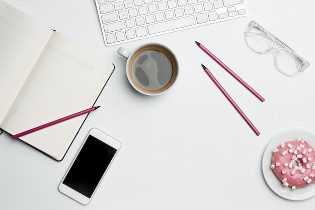 Mesa de escritorio de oficina con computadora, suministros, teléfono y taza de café.