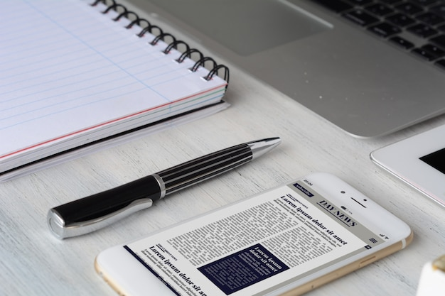 Mesa de escritorio de oficina con computadora, tableta, suministros y noticias de última hora en teléfonos inteligentes