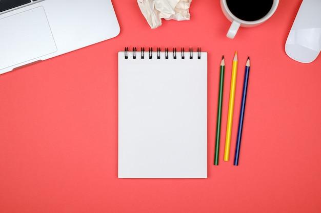 Mesa de escritorio de oficina de diseño moderno con página de cuaderno en blanco, computadora portátil y taza de café