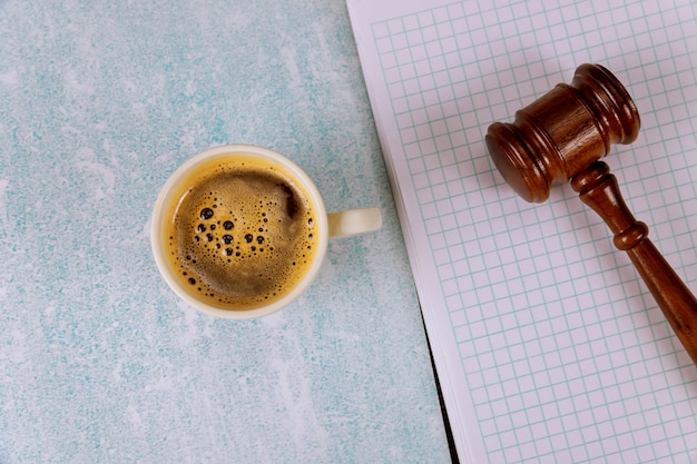 Mesa de escritorio de oficina de justicia legal con suministros, taza de café en un juez martillo de ley