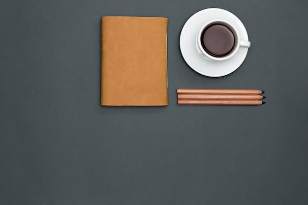 Mesa de escritorio de oficina con lápices, cuaderno y una taza de café.