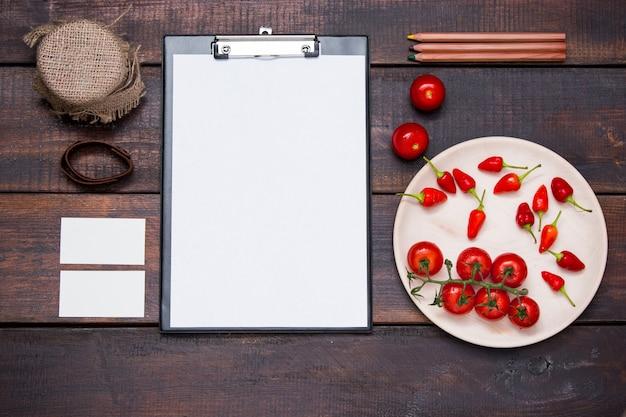 Mesa de escritorio de oficina con lápices, suministros y verduras.