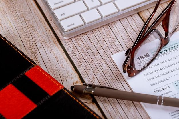 Mesa de escritorio de la oficina del lugar de trabajo en la oficina del contador impuesto sobre la renta de ee. uu. formulario 1040 con gafas y bolígrafo en el teclado de la computadora