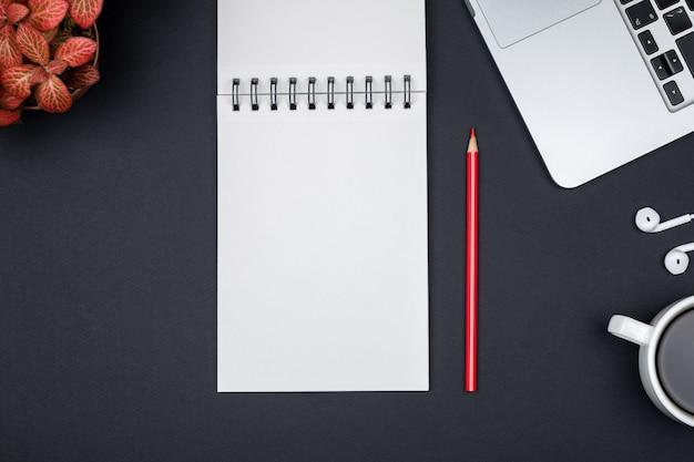 Mesa de escritorio de oficina moderna con laptop y página de cuaderno en blanco