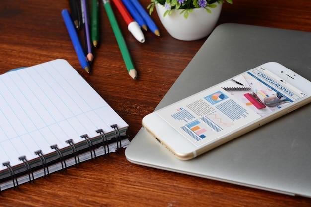 Mesa de escritorio de oficina con pantalla de teléfono inteligente con estadísticas sobre el crecimiento de la empresa