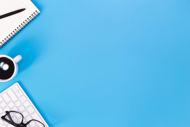 Mesa de escritorio de oficina plana del lugar de trabajo moderno con computadora portátil en la mesa azul, vista superior del fondo del ordenador portátil y espacio de copia sobre fondo negro, escritorio azul con ordenador portátil