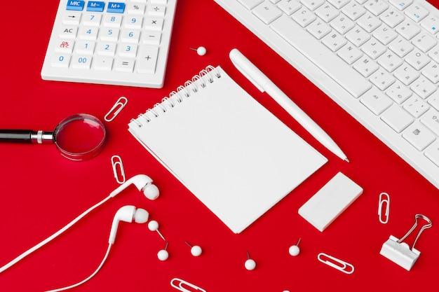 Mesa de escritorio de oficina rojo con cuaderno en blanco, teclado y suministros. vista superior con espacio de copia. endecha plana.