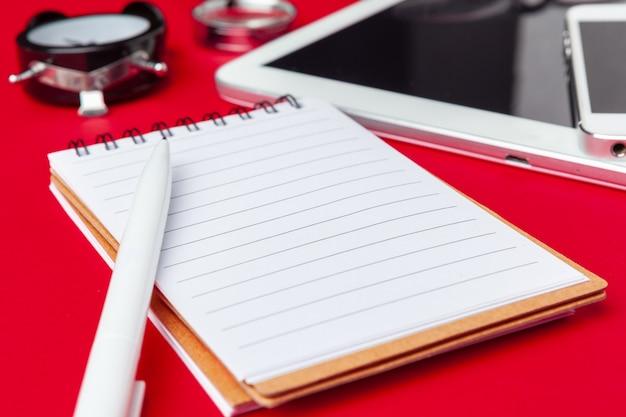 Mesa de escritorio de oficina rojo con cuaderno en blanco, teclado y suministros.