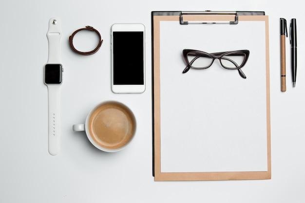 Mesa de escritorio de oficina con taza, suministros, teléfono en blanco