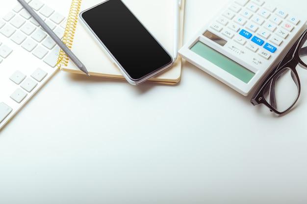 Mesa de escritorio de oficina con teclado de computadora, suministros, calculadora, bolígrafo, gafas
