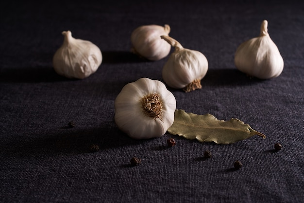 En la mesa de estilo negro, condimentos: cebolla, ajo, guisantes de pimienta negra y laurel