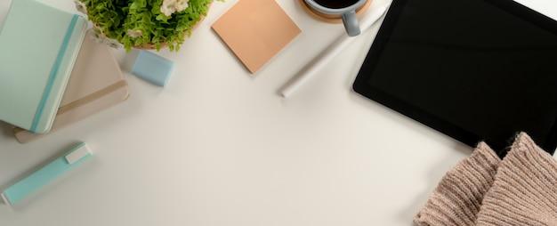 Mesa de estudio con espacio de copia, tableta digital, papelería y decoración en escritorio blanco