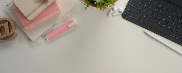 Mesa de estudio con espacio de copia con tableta digital, papelería y decoraciones en mesa blanca
