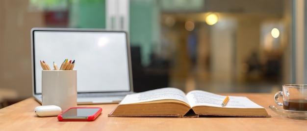 Mesa de estudio con libro abierto, maqueta de computadora portátil, teléfono inteligente, papelería y taza de café