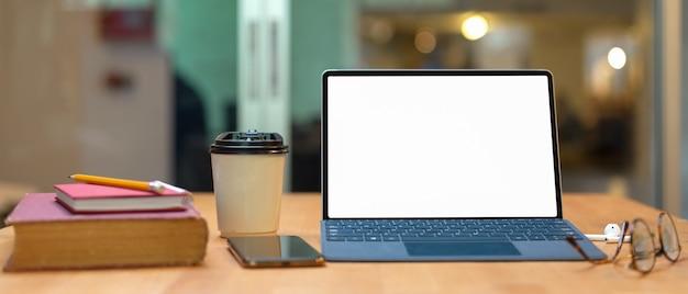 Mesa de estudio con libros, tableta simulada con teclado, teléfono inteligente, gafas y vaso de papel