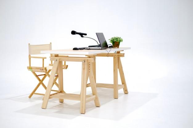 Mesa de estudio de madera con laptop y micrófono.