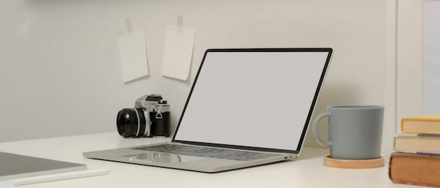 Mesa de estudio con maqueta portátil, libros, taza de café, cámara y tableta digital en mesa blanca