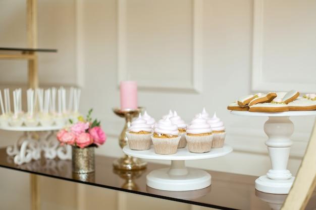 Mesa para eventos con dulces, decoración minimalista con flores frescas.