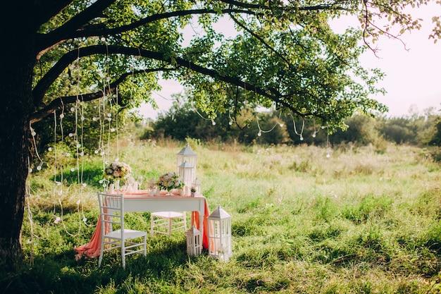 Mesa festiva bellamente decorada en el parque al atardecer, cena de boda romántica.