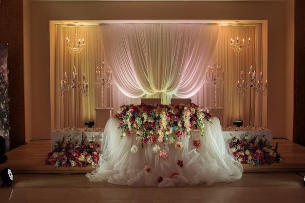 Mesa festiva decorada con composición de flores blancas, rojas y rosadas y vegetación en el salón de banquetes.